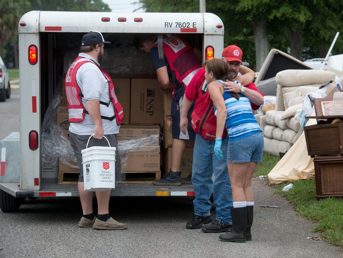 Gulf Breeze resident Lynette Dewberry, far right, thanks Mike Craig of the Salvation Army after being offered a free pair of rubber boots and cleaning supplies from the organization Friday afternoon May 9, 2014.