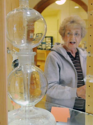 """Pattie Frohnapfel, Archives Director at the Ohio Glass Museum, discusses the new exhibit """"Through the Looking Glass"""" Friday at the Ohio Glass Museum in downtown Lancaster."""