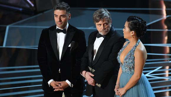 Oscar Isaac (left) presents at the 90th Academy Awards