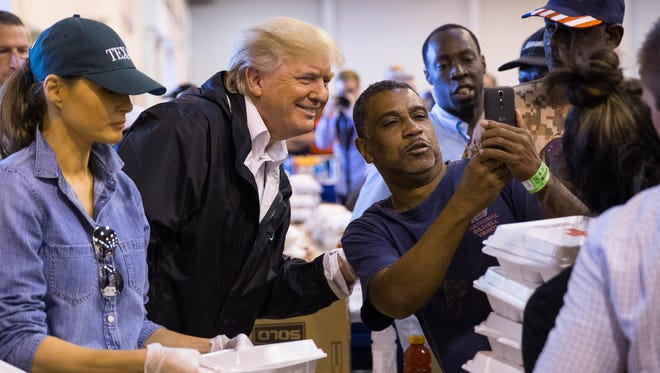 President Trump takes a photo with a man as he hands out food at the NRG Center in Houston where he met with evacuees from Hurricane Harvey.