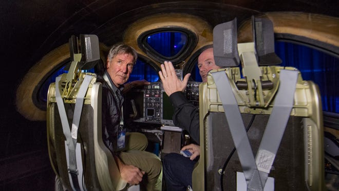 Actor and pilot Harrison Ford, left, listens to Virgin Galactic chief pilot Dave Mackay inside the new SpaceShipTwo space tourism rocket from Virgin Galactic. The VSS Unity was unveiled Friday in Mojave, California.