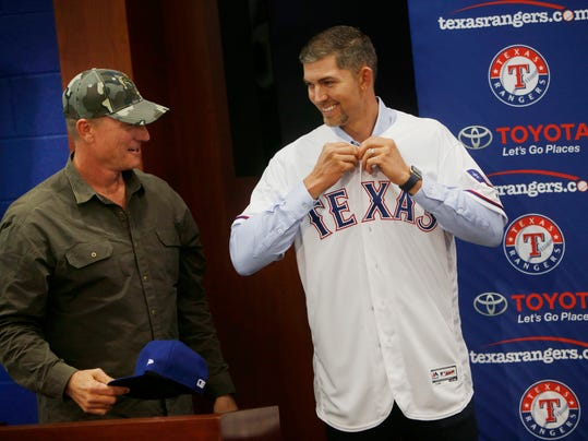 Newly signed Texas Rangers pitcher Mike Minor puts on a Rangers jersey next to Texas Rangers Manager Jeff Banister before a press conference at Globe Life Park in Arlington, Texas, Wednesday, Dec. 6, 2017. A day after meeting in Los Angeles with Japanese pitcher and outfielder Shoehi Ohtani, Rangers officials were back home in Texas and introduced left-hander Mike Minor. The likely starter signed a $28 million, three-year contract. (Rose Baca/The Dallas Morning News via AP)