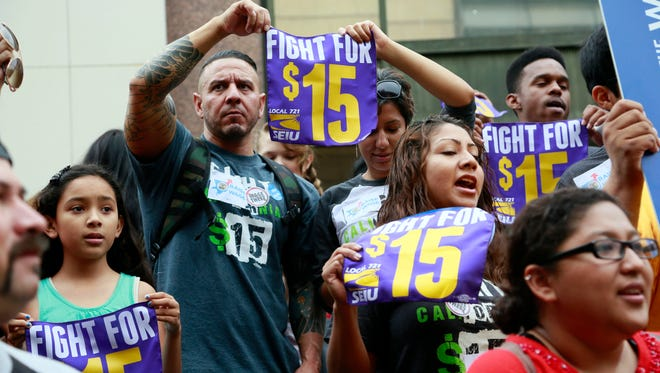 In this Tuesday, July 21, 2015 photo, workers hold a rally in Los Angeles in support of the Los Angeles County Board of Supervisors' proposed minimum wage ordinance. On Saturday, March 26, California legislators and labor unions reached an agreement that will take the state's minimum wage from $10 to $15 an hour.