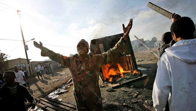 South Africans cheer as they turn over a container belonging to a foreigner as they riot in the Reiger Park informal settlement outside Johannesburg Monday May 19, 2008.