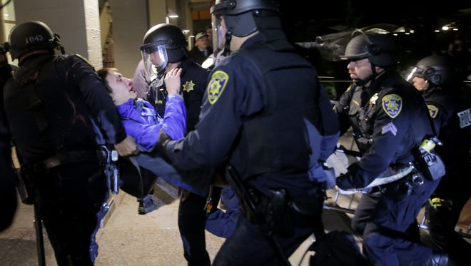 A protester is carried into a building by police officers during a protest on the University of California, Berkeley campus on Feb. 1, 2017, to protest a planned speech by controversial Breitbart News writer Milo Yiannopoulos.
