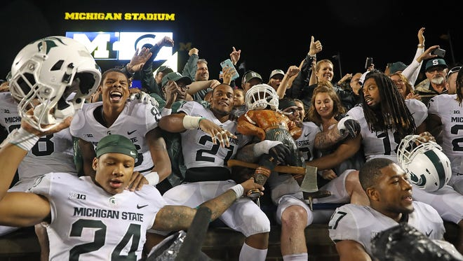 Michigan State's Gerald Holmes (24) and his teammates celebrate in the stands with Spartans fans and the Paul Bunyan Trophy after defeating Michigan, 14-10, at Michigan Stadium on Oct. 7, 2017 in Ann Arbor.