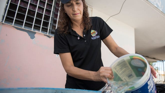 Michelle Rebollo transfers water from one barrel to another, she is collecting rainwater from her downspouts because her family has been without running water for the past seven weeks.