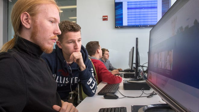 Pine Forest High School senior Josiah Robinson, left, and junior Jan Engelmann work together on an exercise while participating in the CyberPatriot National Youth Cyber Education Program at the University of West Florida on Friday, Jan. 19, 2018. Many of the Pine Forest students will participate in the CyberThon competition March 9-11.