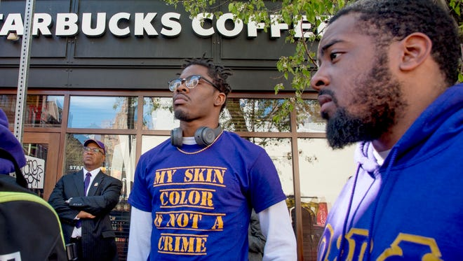 Omega Psi Phi Fraternity members Reese Tillman, right, and Bucketo Mitchell listen during a rally, Sunday, April 22, 2018, outside the Starbucks where one of their fraternity brothers was one of the two black men arrested.