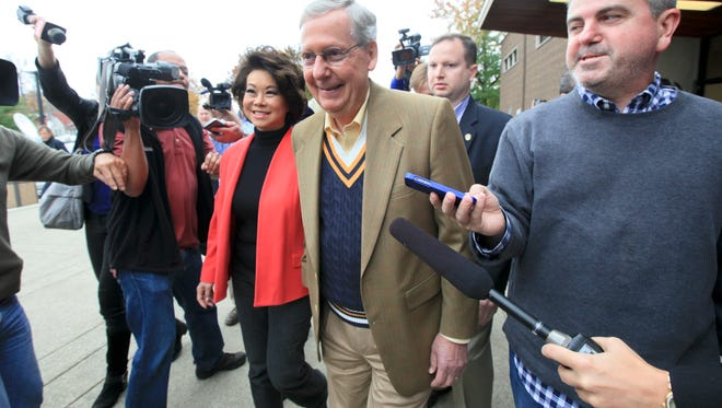Senator Mitch McConnell and wife, Elaine Chao, is swarmed by media after casting their votes at Bellarmine University.November 4, 2014