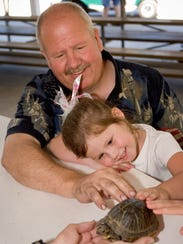 Gary Pohlhammer, of Muskego, holds his 4-year-old granddaughter,