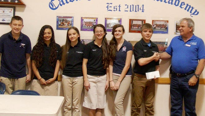 The student council of Calvary Christian Academy raised funds in their daily school snack bar and presented a donation of $600 to Randy Salars, at right, for the Silver City Gospel Mission's winter men's shelter. Pictured are students, from left, Jadaniah Tarpley, Julia Mathieu, Emma Eng, Autumn Laws, Kensi Wheeler, Seth Neal.