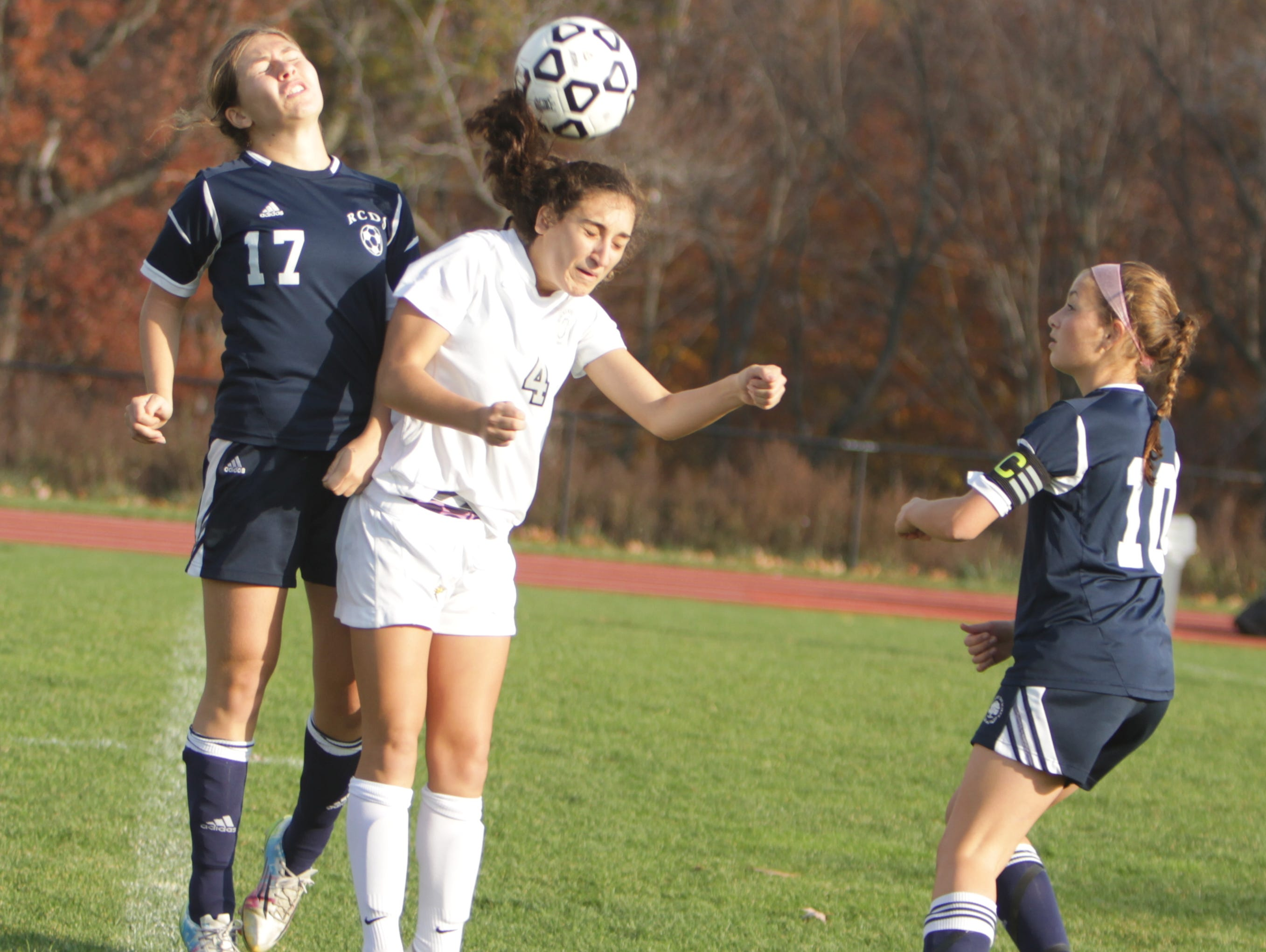 Hackley's Kat Cucullo (4) heads the ball away from Rye Country Day's Therese Mooney (17) during a NYSAIS semifinal match at the Hackley School on Friday, November 6th, 2015. Hackley won 3-1.