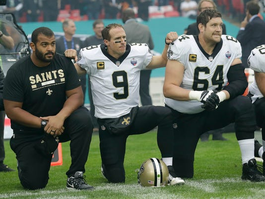 New Orleans Saints quarterback Drew Brees (9) kneels down with teammates before the U.S. national anthem was played ahead of an NFL football game against the Miami Dolphins at Wembley Stadium in London, Sunday Oct. 1, 2017. Saints players then stood when the anthem was played. (AP Photo/Tim Ireland)