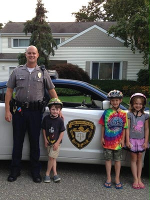 """Officer Adam Koeppen poses with Brennan Hutton, Tommy Renkin, and Keri Renkin after issuing each of the youngsters """"summonses'' good for a free ice cream for wearing their bicycle helmets."""