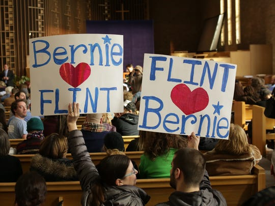 Kade Katrak and his mother Patrice Katrak of Fenton hold up signs showing support for democratic presidential candidate Bernie Sanders at Woodside Church in Flint on Thursday February 25, 2016 while waiting for a community forum with Sanders to start.