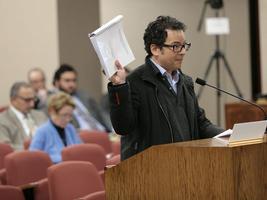 Max Grossman holds up a study of Union Plaza's historical buildings as discussion on the placement of the Downtown arena continues Monday. Later that day, the El Paso County Commissioners Court did not reappoint Grossman to the El Paso County Historical Commission.
