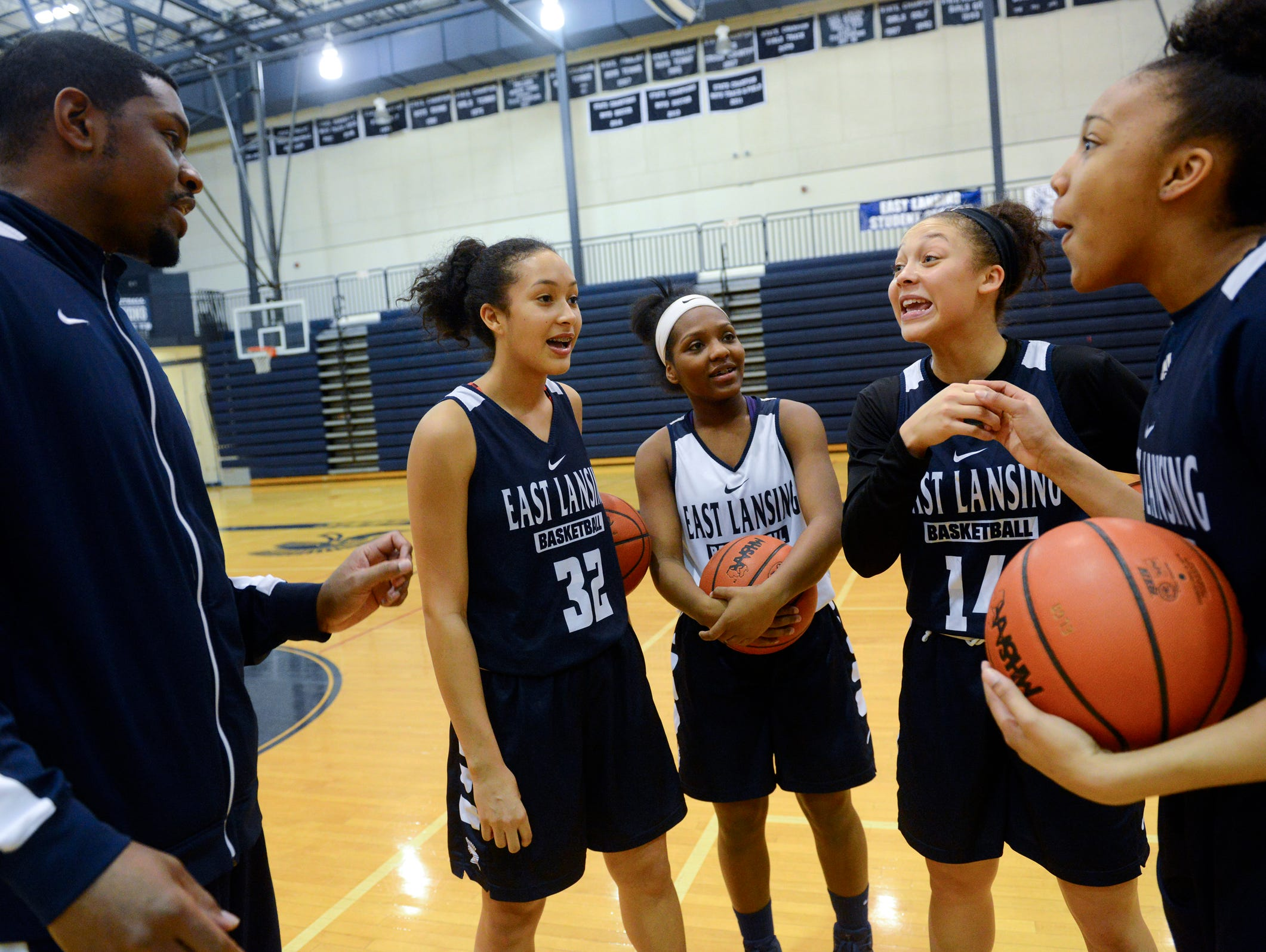 From left to right, Bill Hamilton, an assistant coach, Aaliyah Nye, Kalaia Hampton, Aazh Nye and Jaida Hampton chat during practice on Thursday, Feb. 23, 2017 at East Lansing High School. Aaliyah and Aazh are sisters. Kalaia and Jaida are sisters as well.