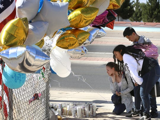 Parkland Middle School students Samantha Hood, bottom, Yalyssa Reyes and Alex Moreno visit a memorial erected for sixth-grader Jonathan Benko, who was struck and killed by a vehicle after leaving campus during a rally against gun violence at schools.