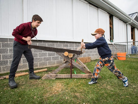 Jeffrey Baker, 14, left, saws through a piece of wood