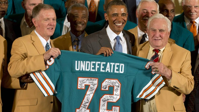 Former Miami Dolphins football quarterback Bob Griese, left, President Barack Obama and 1972 Dolphins Coach Don Shula, right, hold a signed jersey in the East Room of the White House in Washington, Tuesday, Aug. 20, 2013, during a ceremony honoring the Super Bowl VII football Champion Miami Dolphins. The 1972 Miami Dolphins remain the only undefeated team in NFL history. Form left are, Griese, wide receiver Paul Warfield, the president, running back Larry Csonka and Shula.