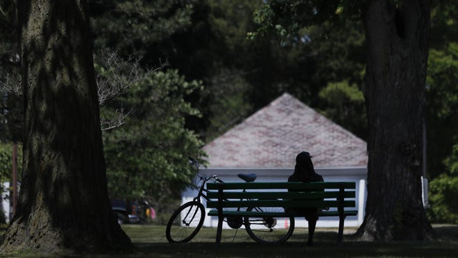 FILE - In this June 29, 2020 file photo, a cyclist sits on a Hoyt Park bench in Saginaw, Mich. It has been months since many people first learned what a shelter-in-place order even meant. As restrictions are slowly lifted, it's now time to reflect. This is a meaningful opportunity to learn from what we've all experienced. Experts explore some of the financial repercussions of this pandemic, including what Americans have been learning in the process, and how they'll likely apply these lessons to life after the outbreak is over.