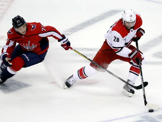 Washington Capitals right wing T.J. Oshie (77) defends against Carolina Hurricanes center Elias Lindholm (28), from Sweden, in the third period of an NHL hockey game, Thursday, Jan. 11, 2018, in Washington. (AP Photo/Alex Brandon)