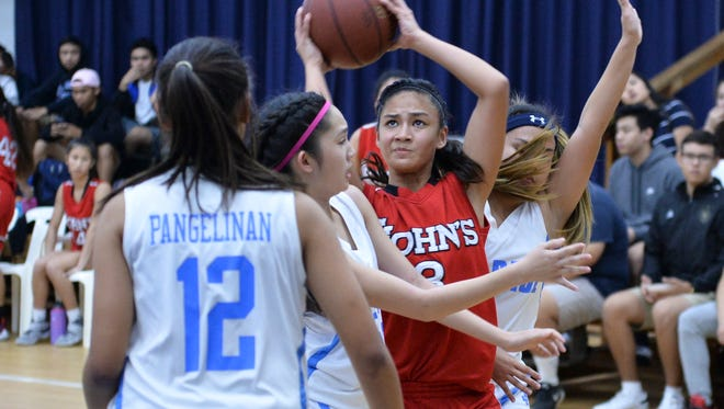 Monica Giger of the St. John's Knights fights through a triple-team in an Independent Interscholastic Athletic Association of Guam Girls Basketball League playoff match against the St. Paul Warriors at St. Paul on Nov. 26, 2016. Giger led her team in rebounds despite playing with an injured foot.