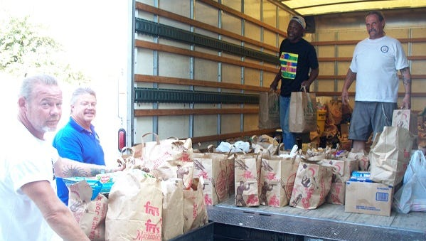 Community members are dropping their food donation at a Tempe Community Action Agency's food drive.