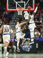 Kansas forward Jamari Traylor, right, blocks a shot by Connecticut's Jalen Adams during the first half Sat. March 19, 2016, of their NCAA Div. I men's basketball championship second round game at Wells Fargo Arena, in Des Moines, Iowa.