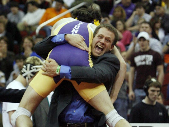Jordan Gacke jumps into the arms of one of his coaches,