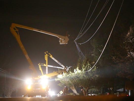 Crews work on power lines Tuesday near Crockett County