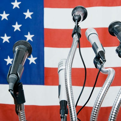 Microphones by American flag.