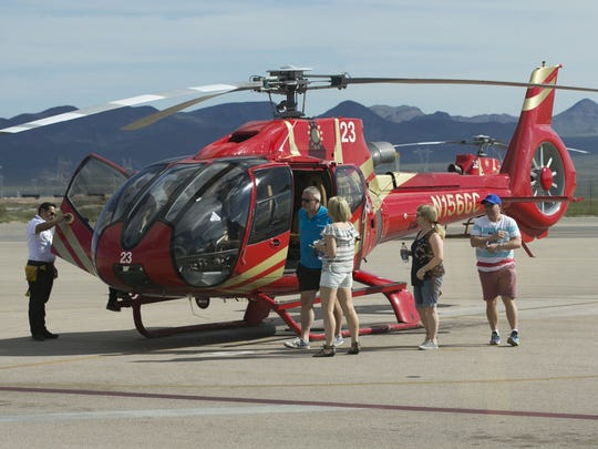 Passengers get off a Papillon Grand Canyon Helicopter after flying to the western part of Grand Canyon National Park, at the airport in Boulder City, Nevada.