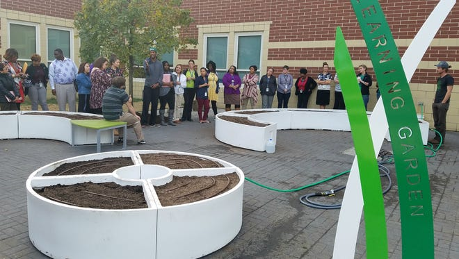 Teachers at Global Prep Academy in Indianapolis learn how to maintain learning gardens that workers with The Kitchen Community installed Nov. 17, 2016.