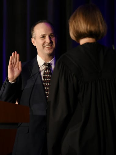 Lansing Mayor Andy Schor is sworn in by the Hon. Louise