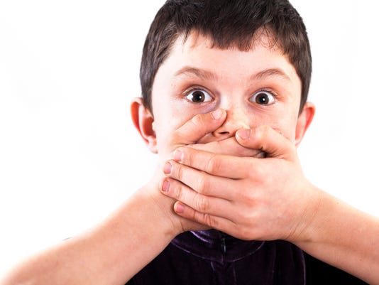 Shocked boy  with hands over mouth