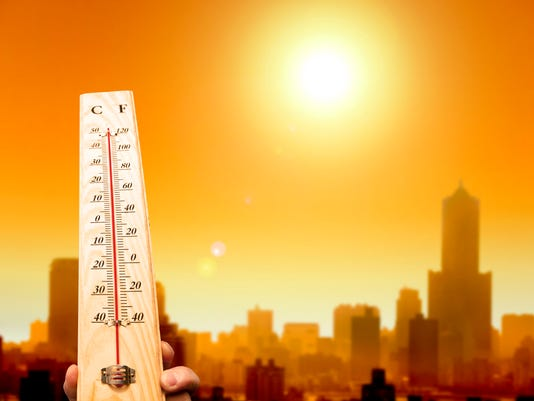 heatwave in the city and hand showing thermometer