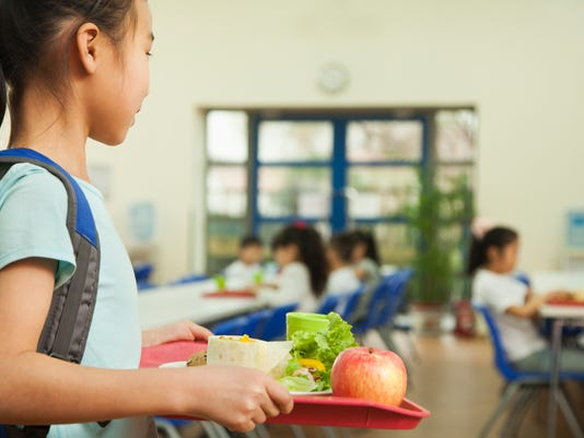 Girl holding food tray in school cafeteria