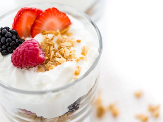 Greek yogurt topped with granola and fresh berries.