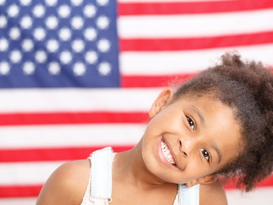 Cute preschool girl smiling in front of USA flag