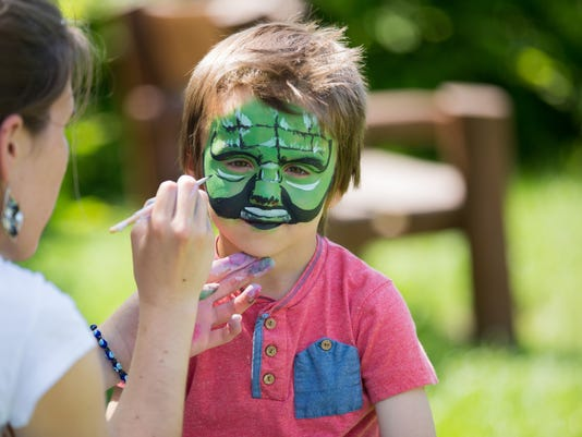 Cute little five years old boy, having his face painted