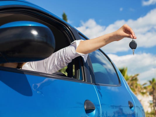 Young woman holding keys of new car