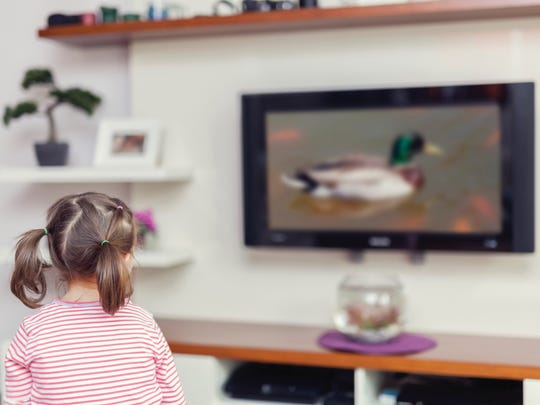 A little girl watches TV in her living room.