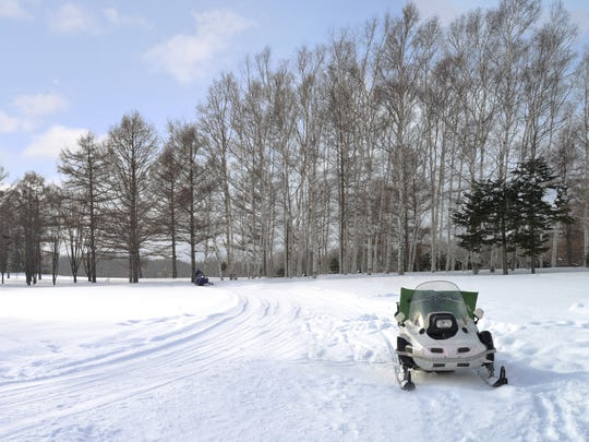A snowmobile sits on a snow-covered trail.