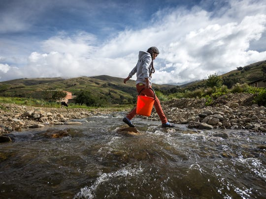 Rocio Lopez Orosco, 11, walks over a polluted river