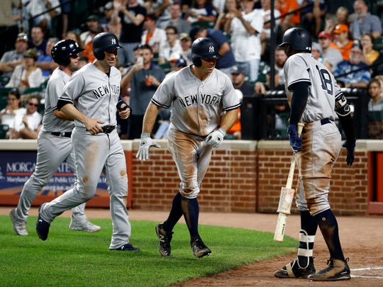 New York Yankees' Brett Gardner, second from right, and Neil Walker, second from left, greet teammate Didi Gregorius (18) after Gardner batted in Walker on a home run in the fourth inning of the second baseball game of a doubleheader against the Baltimore Orioles, Monday, July 9, 2018, in Baltimore.