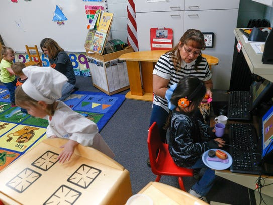 Preschool students work with their education assistants on Friday at Lydia Rippey Elementary School in Aztec.