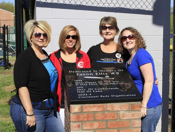 Jason's family stands behind the memorial bearing his name next to the home dugout.  From left are sister Kelly Ellis Eastman, wife Amy Ellis, mother Pam Ellis Dearwester, and sister Lacey Ellis Young.  The Glen Este Trojan baseball team held a special ceremony retiring his No. 9 as well as unveiling a memorial next to the home dugout in honor of the slain police officer.