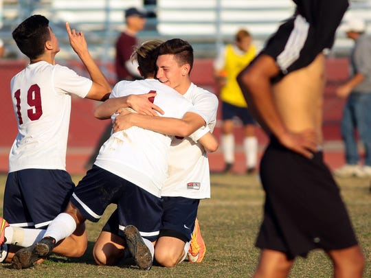 La Quinta High School's  Carlos Ortega (19,white, left), Isaac Sanchez (4, white, center) and Daniel Alexander (15, white, right) celebrate on the field and hug each other as a Sunny Hills player walks off the field with his jersey pulled over his head following the Blackhawks' 1-0 CIF semifinal playoff victory at home on Tuesday afternoon, March 3, 2015. La Quinta advances to the CIF title game, which will be held later this week.